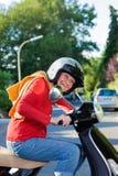 Livlig äldre kvinna som rider en sparkcykel Arkivbild