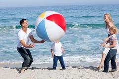 Livlig familj som leker med en boll Arkivbild