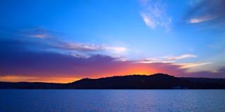 Livlig karmosinröd och blå Seascapesolnedgång med vattenreflexioner Royaltyfri Foto