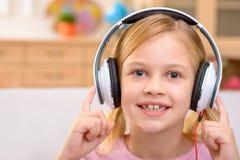 Livlig liten flicka som lyssnar till musik Fotografering för Bildbyråer