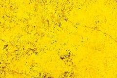Livlig ljus gul vägg för färgfasadsten med skönhetsflar och sprickor som en tom lantlig och enkel bakgrund royaltyfria bilder