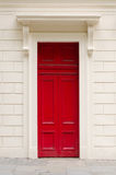 Livlig röd dörr på en vit vägg Royaltyfri Foto