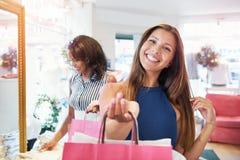 Livlig shoppare för ung kvinna som grinar på kameran royaltyfria foton