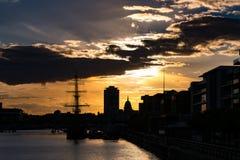 Livlig solnedgång i Dublin, Irland som ser över floden Liffey med byggnader, och Dublin Spire i kontur royaltyfri bild