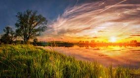 Livlig vårsoluppgång Fjädra landskapet av gryning över floden med glänsande grönt gräs på kust Arkivfoto