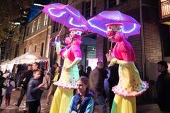Livliga Sydney 2015: kvinnor på styltor med elektriska paraplyer Royaltyfri Bild