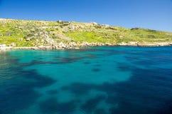 Livligt blått vatten i hamn nära staden Mgarr i den Gozo ön, Malt royaltyfria foton