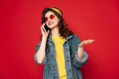 Livligt samtal f?r lycklig hipsterflicka vid mobiltelefonen arkivbild