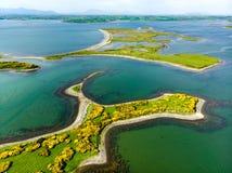 Livligt smaragd-gräsplan vatten och små öar nära den Westport staden längs den lösa atlantiska vägen, Irland royaltyfri foto