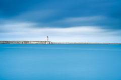 Livorno port lighthouse, breakwater and soft water under cloudy sky. Tuscany, Italy, Europe. Long exposure photography stock photos
