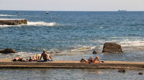 Some people sunbathe out on the pier in the sea of Livorno. Pano royalty free stock photo