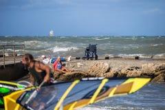 Livorno Włochy, Sierpień, - 2017: Starej Kobiety obsiadanie na skałach blisko linii brzegowych spojrzeń przy Młodym surfingowem n fotografia royalty free