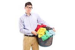 Livrädd ung man som rymmer en tvättkorg Fotografering för Bildbyråer