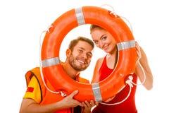 Livräddare i flytväst med cirkelbojet som har gyckel Arkivfoto