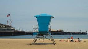 Livräddarehus på en Sandy Beach på havet i blom på en solig dag för sommar som förbiser en pir Royaltyfri Foto