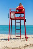 Livräddaren håller klockan på stranden royaltyfri fotografi