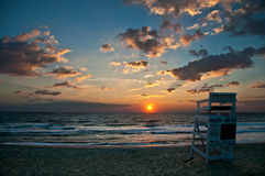 Livräddarestol på stranden på soluppgång Arkivfoto