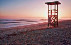 Livräddaretorn, soluppgång, fotspår på den avskilda stranden med berg och lugna hav, playa de muro, alcudia, mallorca, Spanien fotografering för bildbyråer