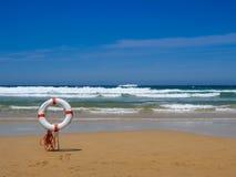 Livräddareutrustning i sand på en strand Arkivbilder