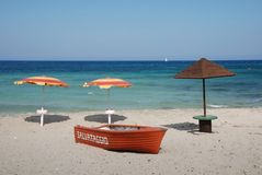 Livräddningsbåt och tre strandparaplyer Fotografering för Bildbyråer