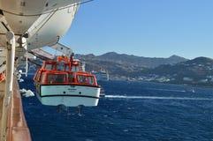 Livräddningsbåt på ett kryssningskepp med den Mykonos ön i utbredd bakgrund Trans. landskap resorkryssningar fotografering för bildbyråer