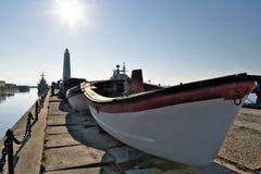 Livräddningsbåtar från krigsskepp på pir i golfen av Finland, Ryssland royaltyfri foto