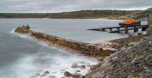 Livräddningsbåtstation och vågbrytare, Sennen liten vik, Cornwall royaltyfri bild