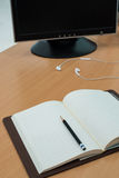Livre, écouteur et ordinateur sur la table en bois Photo stock