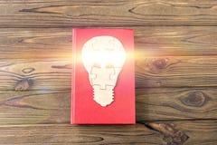 Livre, ampoule électrique des puzzles en bois sur un fond en bois images libres de droits
