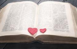 Livre antique et deux coeurs là-dessus Photographie stock libre de droits