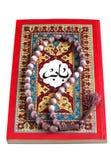 Livre arabe avec le rosaire d'isolement sur un blanc Photos stock