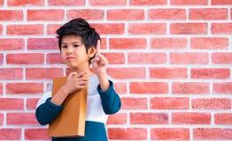 Livre asiatique de participation de garçon sur le fond de mur de briques photographie stock libre de droits