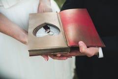Livre avec du charme de vintage avec le coeur fait main auquel mensonge l'anneau Photo stock