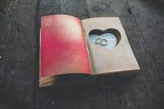 Livre avec du charme de vintage avec le coeur fait main auquel mensonge l'anneau Image stock