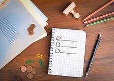 Livre avec la liste de contrôle vide sur la table en bois Photo stock