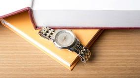 Livre avec la montre photographie stock