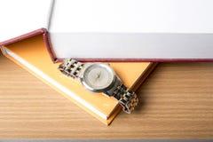 Livre avec la montre images stock
