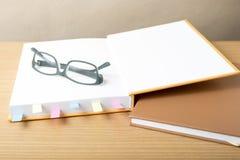 Livre avec la note et les lunettes collantes Photographie stock
