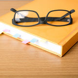 Livre avec la note et les lunettes collantes Photographie stock libre de droits