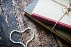 Livre avec les perles en forme de coeur Photographie stock