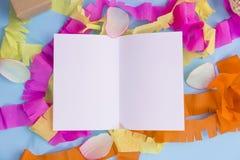 Livre blanc avec le ruban coloré sur le fond bleu Image stock