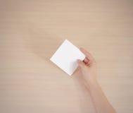 Livre blanc carré se tenant droit dans la main droite feuillet image stock