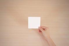Livre blanc carré se tenant droit dans la main droite feuillet photographie stock libre de droits
