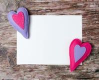 Livre blanc de coeurs colorés fabriqués à la main de feutre sur le fond en bois Images libres de droits