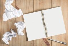 Livre blanc et crayon de papier et gris chiffonné sur le backgro en bois Image stock