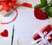 Livre blanc pour la félicitation avec rose et les cadeaux sur la table Photos stock