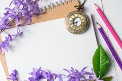 Livre blanc vide avec les fleurs et la montre pourpres de collier de vintage Photos stock