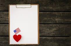 Livre blanc vide sur le presse-papiers en bois avec le coeur rouge et le drapeau américain Photos libres de droits