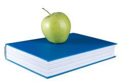 Livre bleu de plan rapproché avec la pomme verte sur le fond blanc d'isolement photo stock