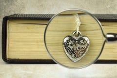 Livre, coeur argenté et loupe Photographie stock